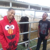 Jerome(left) and his buddy standing next to a horse.